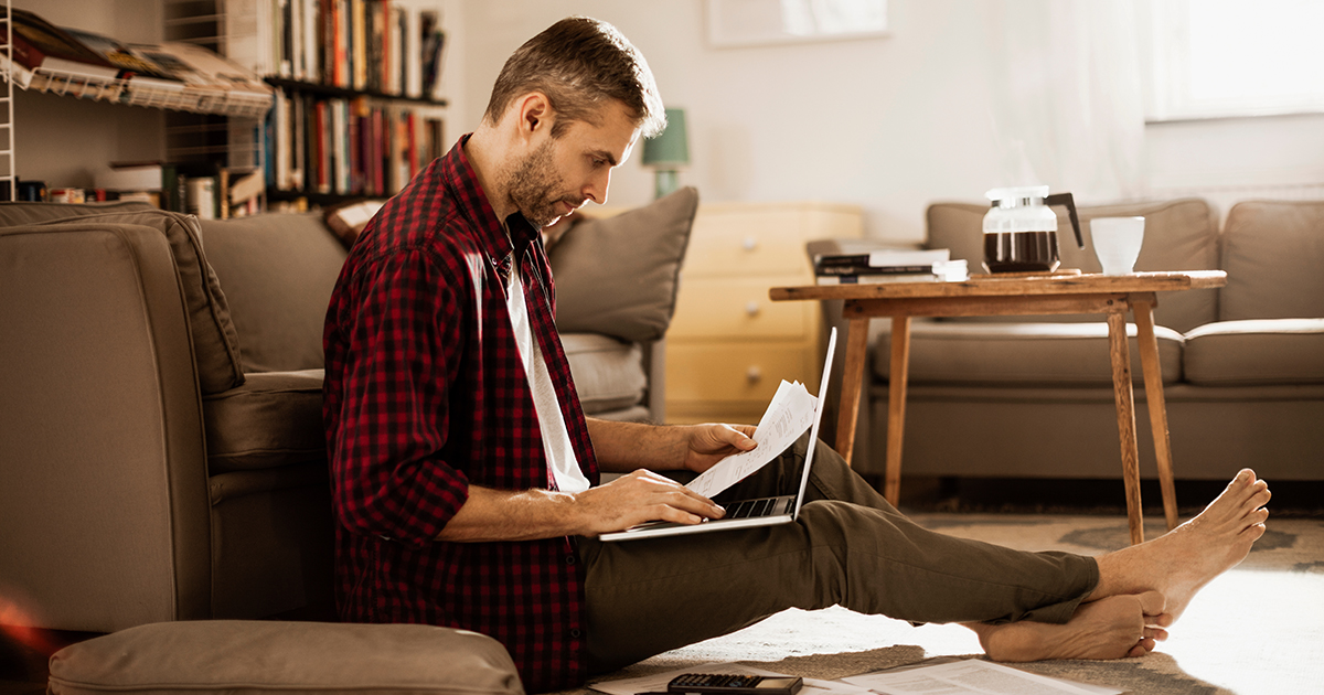 Man sitting on living room floor reviewing documents