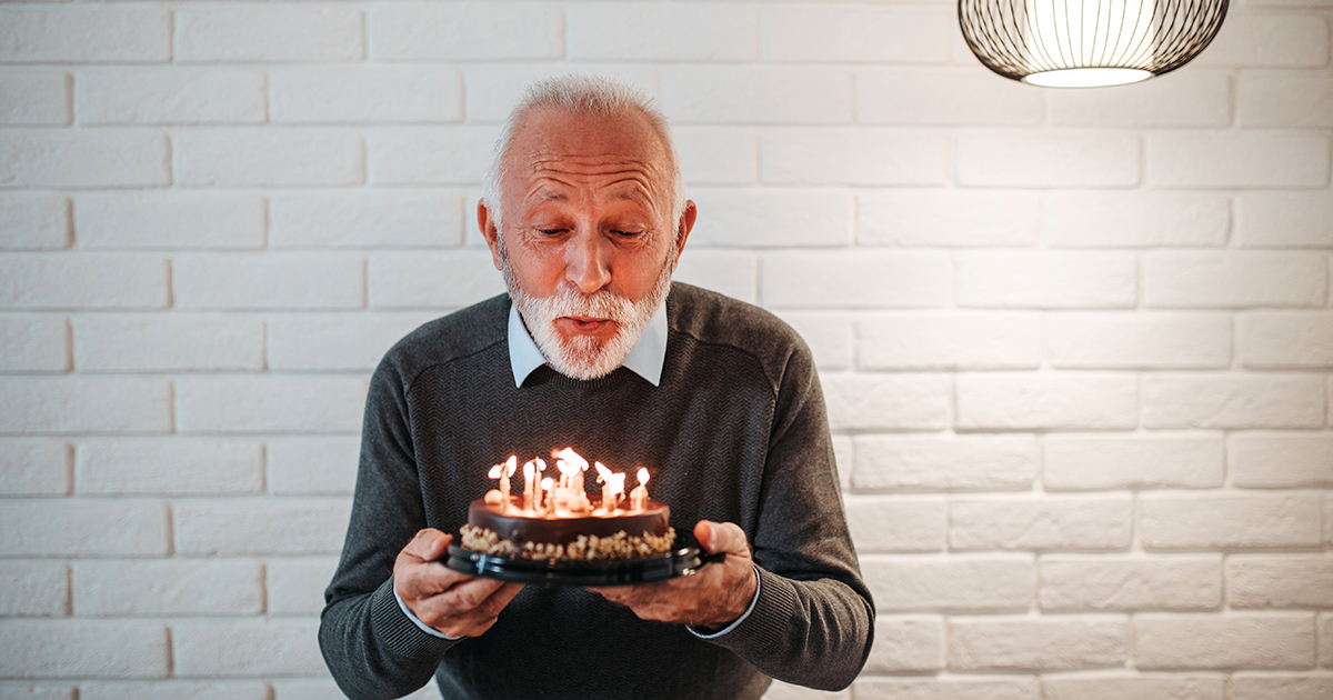 Retiree blowing out candles on birthday cake