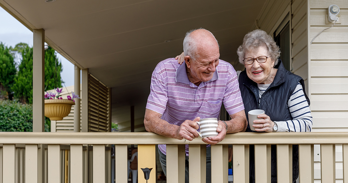 Elderly couple on front porch with coffee cups