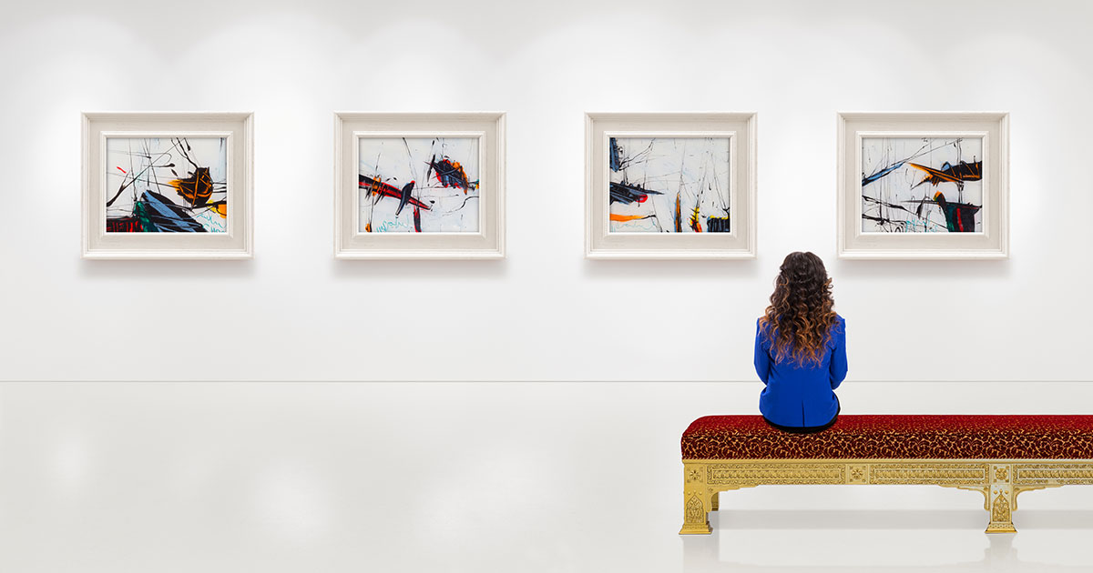 Woman sitting in front of paintings in gallery