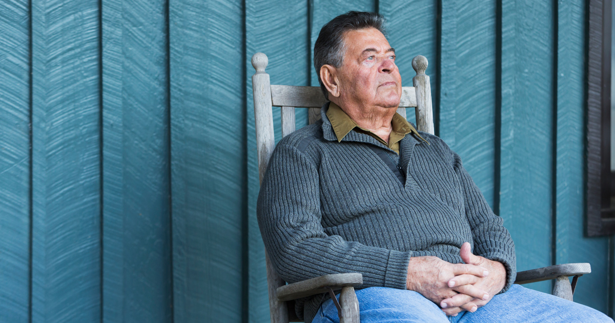 Serious senior man sitting in rocking chair on porch
