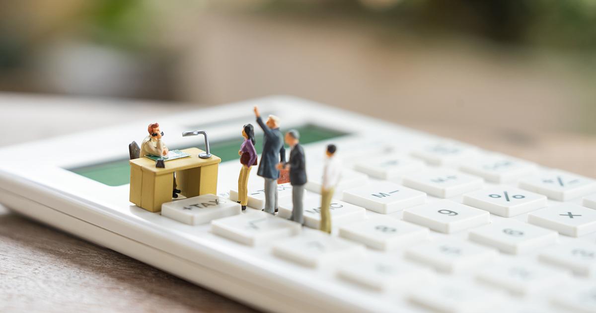 Miniature people queue on calculator