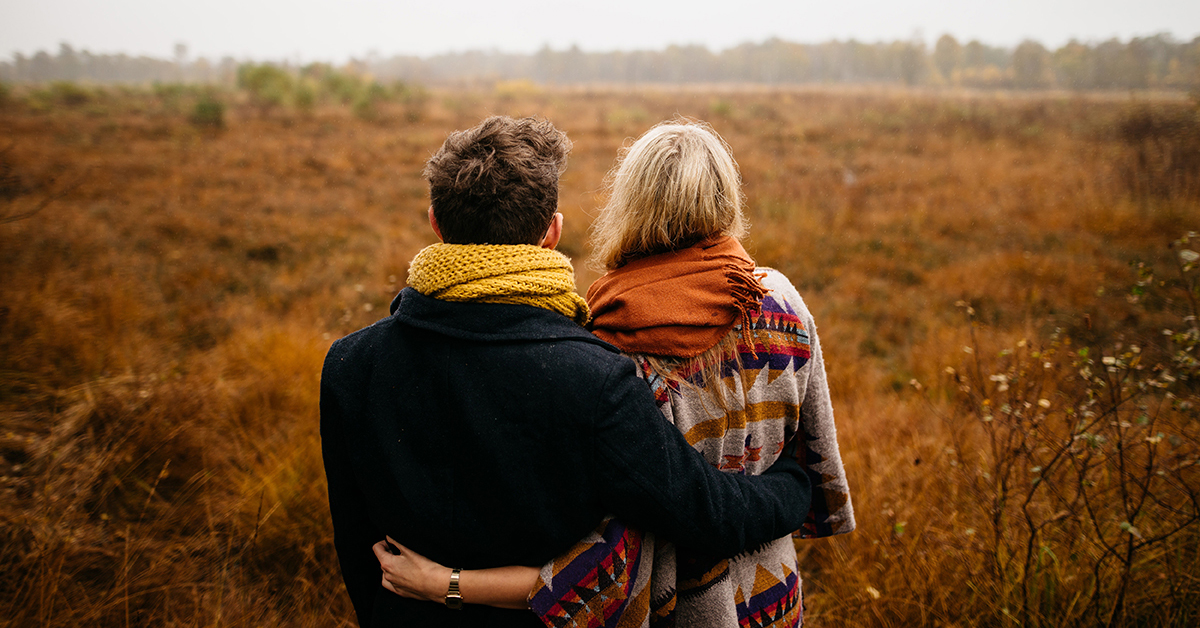 Embracing couple on a field looking into distance