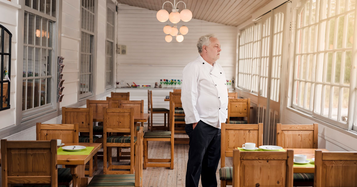 Restaurant owner standing in his empty restaurant