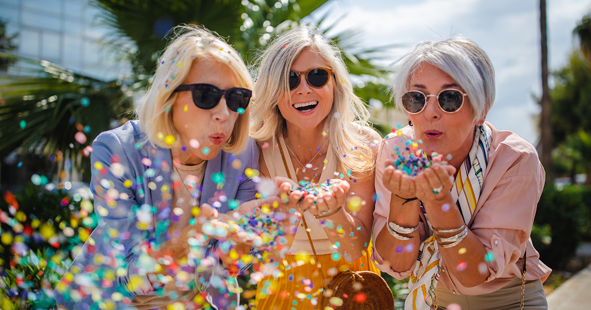 Three ladies celebrating by blowing confetti