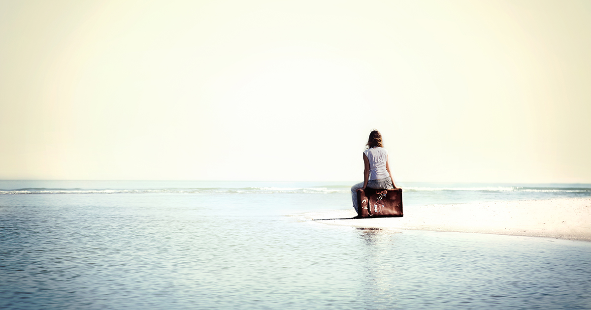 Woman sitting on suitcase next to ocean