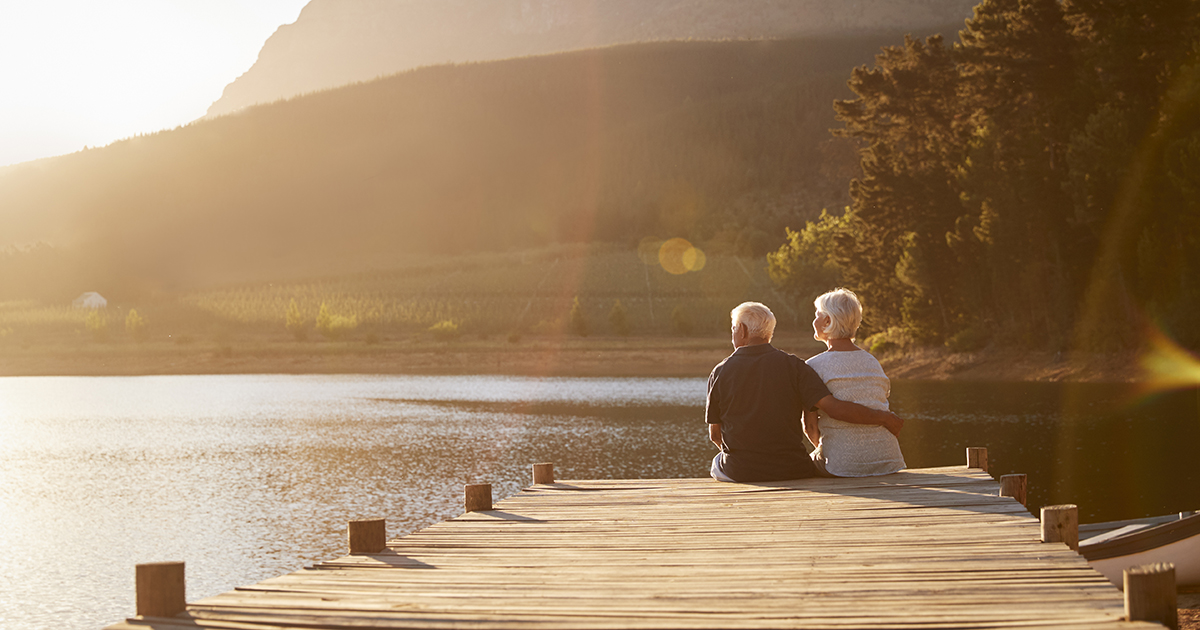 Retired couple sitting on pier