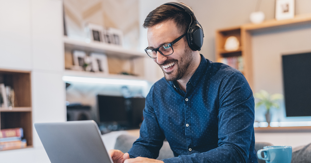 Man listening to webinar and smiling